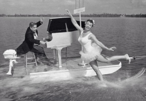 Cypress Gardens founder Dick Pope playing a grand piano on a boat while prima ballerina Willa McGuire rides backwards on her invention, the swivel ski